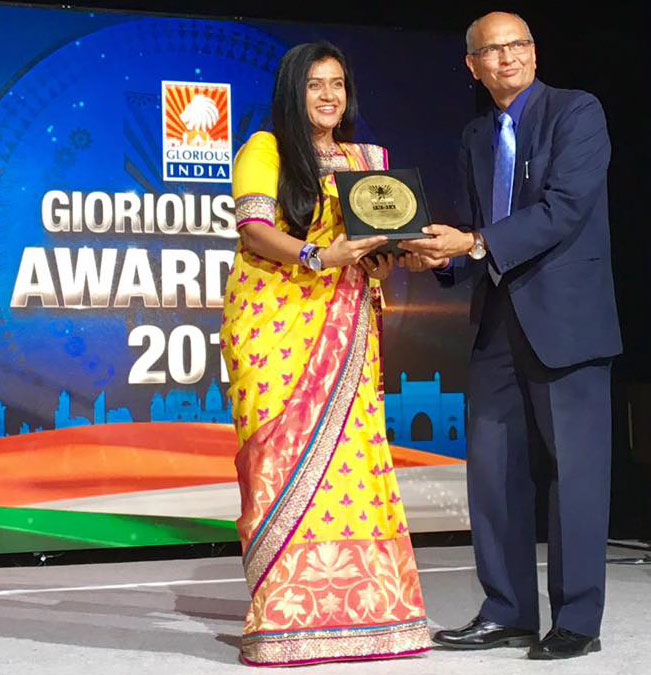 Dr. Joshi accepting an award at the Glorious India Expo